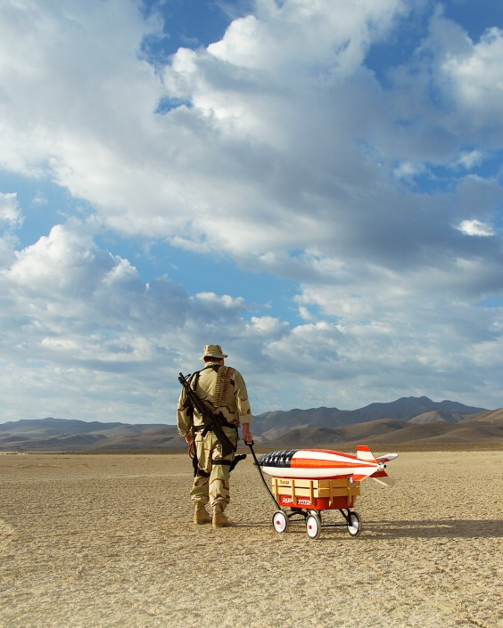 off-to-save-the-world-rusty-humpfreys-bomb-wagon-black-rock-desert-nevada-army-gun-landscape-conceptual